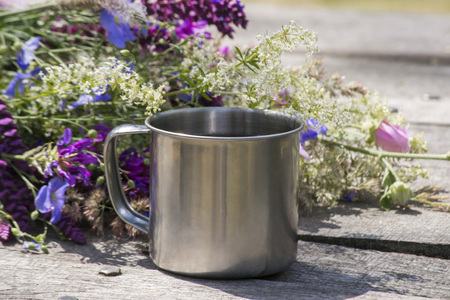 Tourist metal cup next to the flowers stands on a gray wooden table