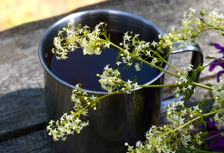 white flower in front of a metal cup on a wooden table