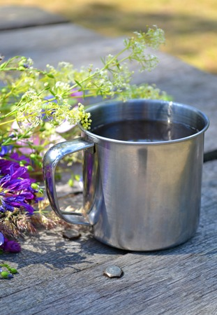 metal cup for a hike on the table beside purple flowers