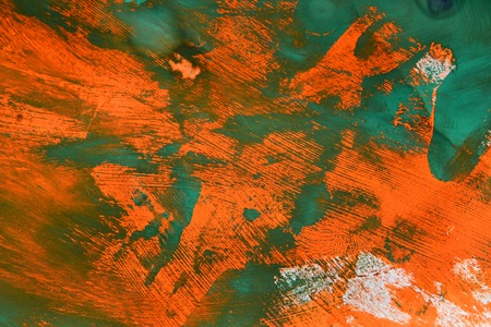 Abstract background of smears of  green over orange paint
