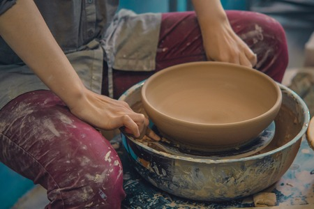 Master Potter holds round clay plate in his hands. Sculptor sculpts pots products from white clay. Workshop pottery. Master crock. Art, creativity. Cultural traditions. Handmade. Craft. Reklamní fotografie