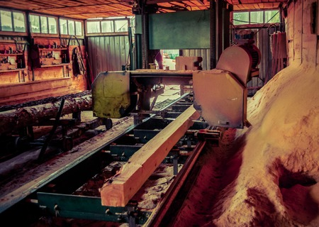 Sawmill. Process of machining logs in equipment sawmill machine saw saws the tree trunk on the plank boards. Wood sawdust work sawing timber wood wooden woodworking 版權商用圖片