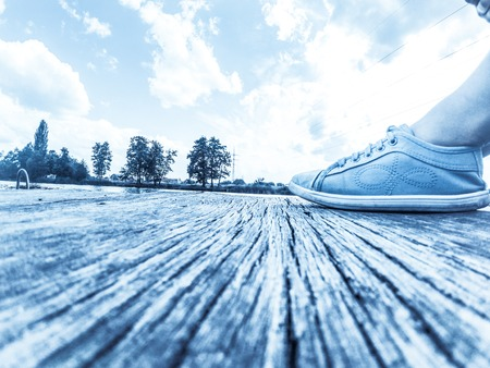 Legs in blue moccasins on a wooden dock Against the backdrop of a blue sky with white clouds 版權商用圖片