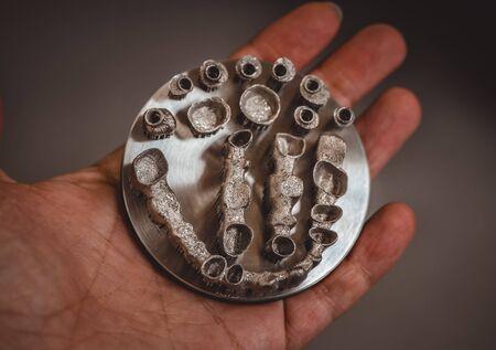 Man is holding object printed on metal 3d printer. Dental crowns created in laser splintering machine close-up. Banco de Imagens