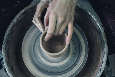 Creating ceramic products of white clay close-up. The sculptor in workshop makes clay jug closeup. Master crock. Twisted potters wheel. Art creativity Cultural tradition Handmade Craft Masters Hands 版權商用圖片