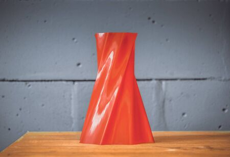 Bright red object vase printed by 3d printer on blue brick wall background. Automatic three dimensional 3d printer performs plastic red colors modeling in laboratory. Modern 3D printing technology.