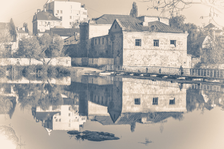 Old vintage photo. Old brick building, river with smooth surface. Mirror reflection. Urban landscape. City landscape