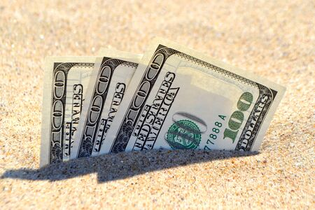 Money dollars half covered with sand lie on beach close-up. Money grows out of the ground. Dollar bills partially buried in sand on sea ocean beach Concept finance money holiday relax vacation. Zdjęcie Seryjne