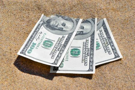 Money dolars half covered with sand lie on beach close-up. Dollar bills partially buried in sand. Three hundred dollars buried in sand on sea ocean beach Concept finance money holiday relax vacation Zdjęcie Seryjne