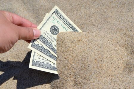 A girl takes out from the sand money notes of three hundred dollars. Concept finance money holiday relax vacation. Sunny summer warm day. A man takes out dollars from sand buried money banknotes