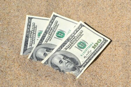 Money dollars half covered with sand lie on beach close-up. Three hundred dollars buried in sand on sea or ocean beach Concept finance money holiday relax vacation. Sunny summer warm wind day.