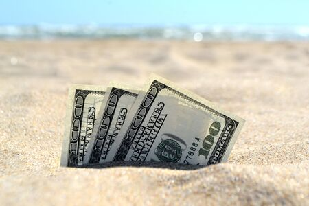 Money dolars half covered with sand lie on sandy beach near sea ocean waves on sunny summer day close-up. Three hundred dollars buried Concept finance money holiday relax vacation.