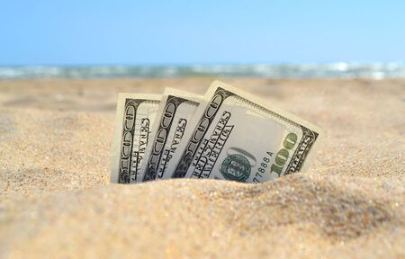 Money dolars half covered with sand lie on sandy beach near sea ocean waves on sunny summer day close-up. Money grows out of the ground. Concept finance money holiday relax vacation.