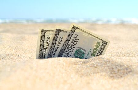 Money dolars half covered with sand lie on sandy beach near sea ocean waves on sunny summer day close-up. Money grows out of the ground. Concept finance money holiday relax vacation. Фото со стока - 137958363