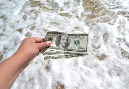 Girl holding money bill of 300 dollars on background of sea oceans waves and sand wet beach close-up on sunny day. Hand waves sea ocean money dollars vacation. Concept finance money holiday traveling Фото со стока