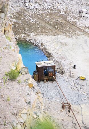 iron rusty shack and blue water in a quarry mining granite