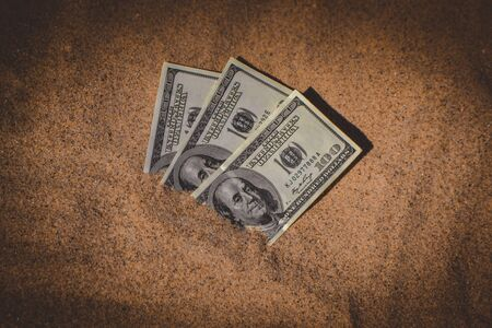Money dolars half covered with sand lie on beach close-up. Three hundred dollars buried in sand on sea or ocean beach Concept finance money holiday relax vacation. Sunny summer warm wind day.