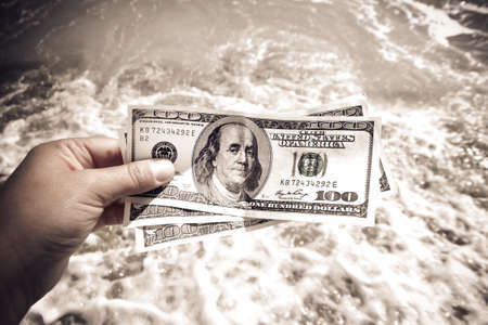 Girl holding money bill of 300 dollars on background of sea oceans waves and sand wet beach close-up on sunny day. Hand waves sea ocean money dollars vacation. Concept finance money holiday traveling Standard-Bild