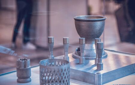Object printed from metal powder on metal 3d printer.Object printed in laser sintering machine. Modern 3D printer printing from metal powder. Progressive additive DMLS, SLM, SLS 3d printing technology Stock Photo