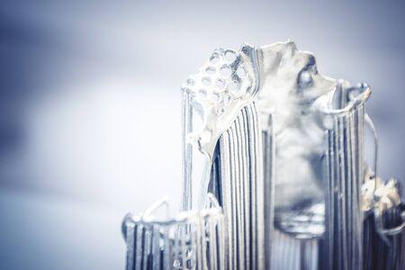 Object printed on metal 3d printer. Dental crowns printed in laser sintering machine. Modern 3D printer printing from metal powder. Concept progressive additive DMLS, SLM, SLS 3d printing technology.