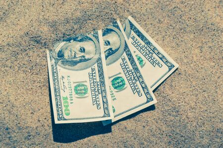 Money dolars half covered with sand lie on beach close-up. Dollar bills partially buried in sand. Three hundred dollars buried in sand on sea ocean beach Concept finance money holiday relax vacation 版權商用圖片