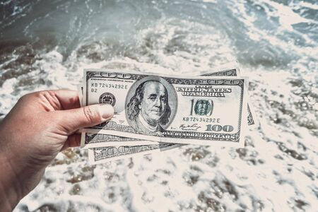 Girl holding money bill of 300 dollars on background of sea oceans waves and sand wet beach close-up on sunny day. Hand waves sea ocean money dollars vacation. Concept finance money holiday traveling 版權商用圖片