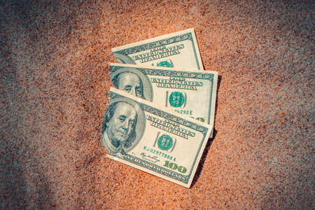 Money dolars half covered with sand lie on beach close-up. Dollar bills partially buried in sand. Three hundred dollars buried in sand on sea ocean beach Concept finance money holiday relax vacation Stock Photo
