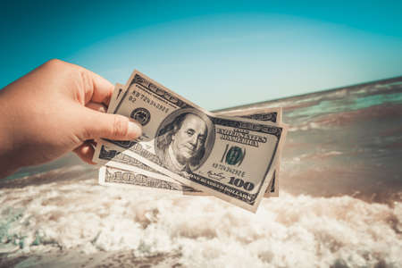 Girl holding a money bill of 300 dollars on background of sea waves and sky on sunny day. Hand waves sea ocean money dollars bills vacation relax summer. Concept finance money holiday horizon skyline