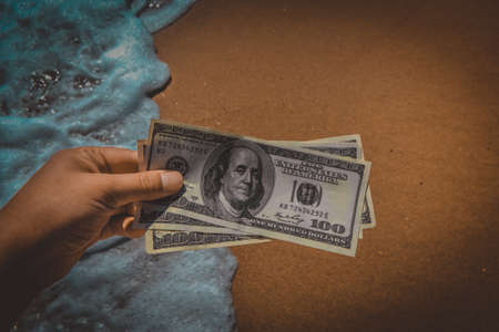 Girl holding money bill of 300 dollars on background of sea ocean waves with white foam and yellow sand wet beach close-up. Hand wave sea ocean money dollars. Concept finance money holiday traveling