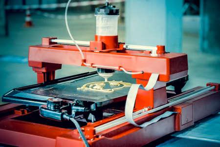 3d printer that printing a liquid dough. 3D printer printing pancakes with liquid dough different shapes close-up. Modern additive technologies 4.0 industrial revolution Standard-Bild