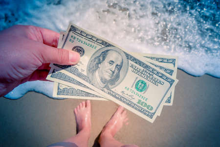 Girl holding money bill of 300 dollars on background of sea ocean waves with white foam and sand wet beach with legs foot in sand close-up. Concept finance money holiday traveling dollars vacation