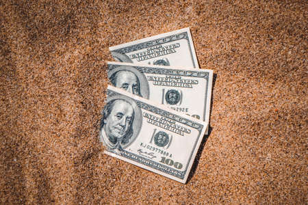 Money dolars half covered with sand lie on beach close-up. Dollar bills partially buried in sand. Three hundred dollars buried in sand on sea ocean beach Concept finance money holiday relax vacation Standard-Bild