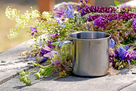 cup of iron stands on a gray wooden table with flowers