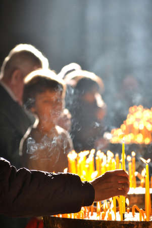 human hand lights a candle in the church Standard-Bild - 167190136