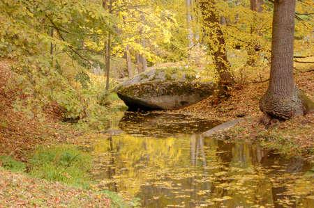 large stone lying near a creek in the autumn in the park, strewn Standard-Bild - 167190145
