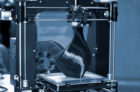 3D printer printing a model in the form of black vase close-up.