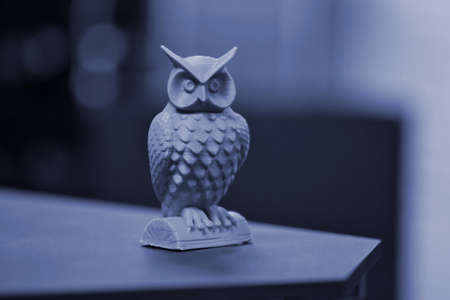 An owl made on a 3d printer stands on a blurry dark background Standard-Bild