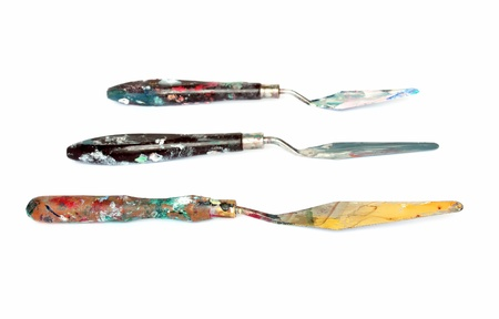 knifes: Three used artist palette knifes on a white background, focus on the one in the front.
