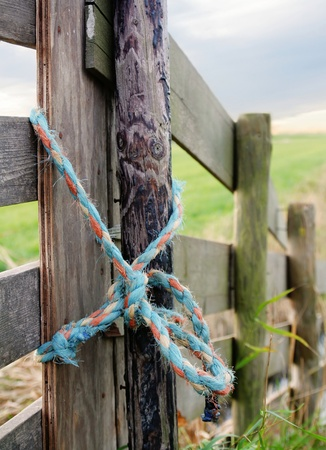 land locked: A rope on a wooden gate by a meadow.