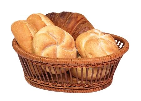 canasta de panes: Varios de pan fresco en una cesta de mimbre de edad aislados en blanco. Foto de archivo