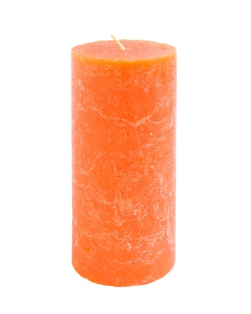 An orange candle isolated on a white background. photo