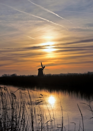 dutch windmill: Dutch landscape with a windmill and a canal at sunset. Stock Photo