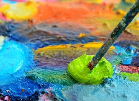 artist painting: Palette with paint and paintbrush, shallow depth of field.