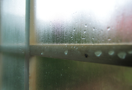 Condensation and raindrops on a window shallow depth of field. Stock Photo