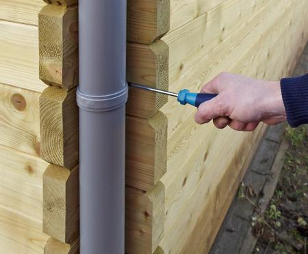 attach?: Mano que sostiene un destornillador para conectar un tubo de drenaje Foto de archivo
