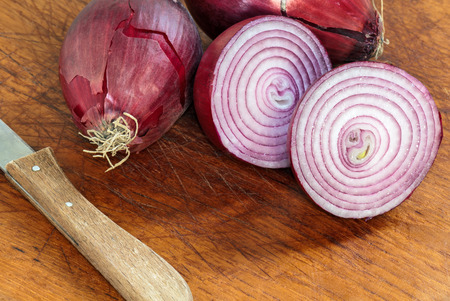 onion slice: Red onions on wooden cutting board.