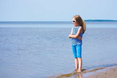 striped vest: Little girl in a striped vest and hat on the beach Stock Photo