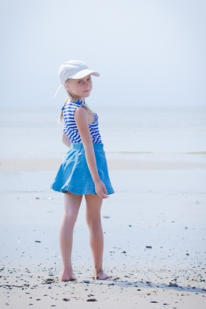 Little girl in a striped vest and hat on the beach photo