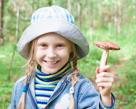 ni�o abrigado: Ni�a linda con el hongo en la mano en el bosque