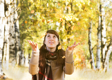 checkered scarf: Beautiful girl in autumn park catch hands falling leaves